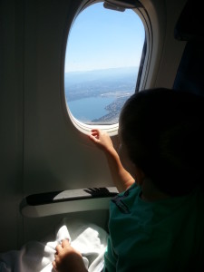 child sits by the window seat on an airplane